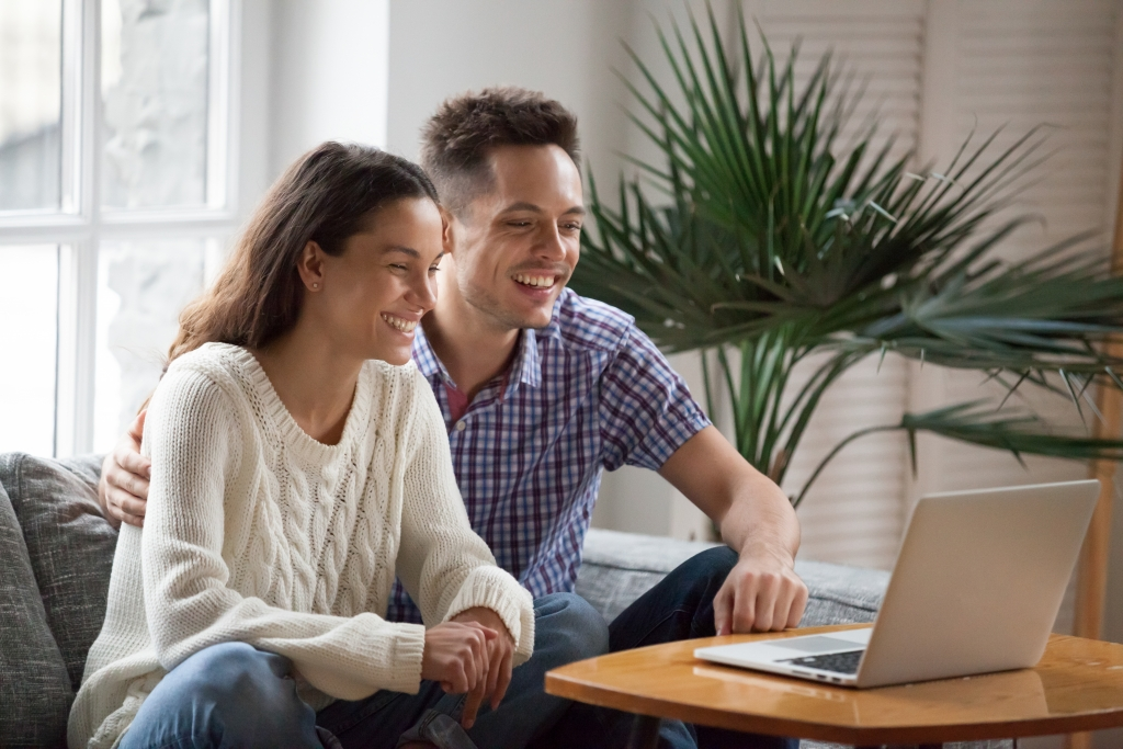 Happy young couple laughing watching funny video or comedy movie online, cheerful man and woman having fun enjoying videocall looking at laptop screen and smiling sitting on sofa at home together