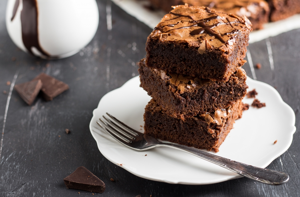 Chocolate brownie cake piece stack on plate homemade pastries sweet cooking with melted chocolate on dark background