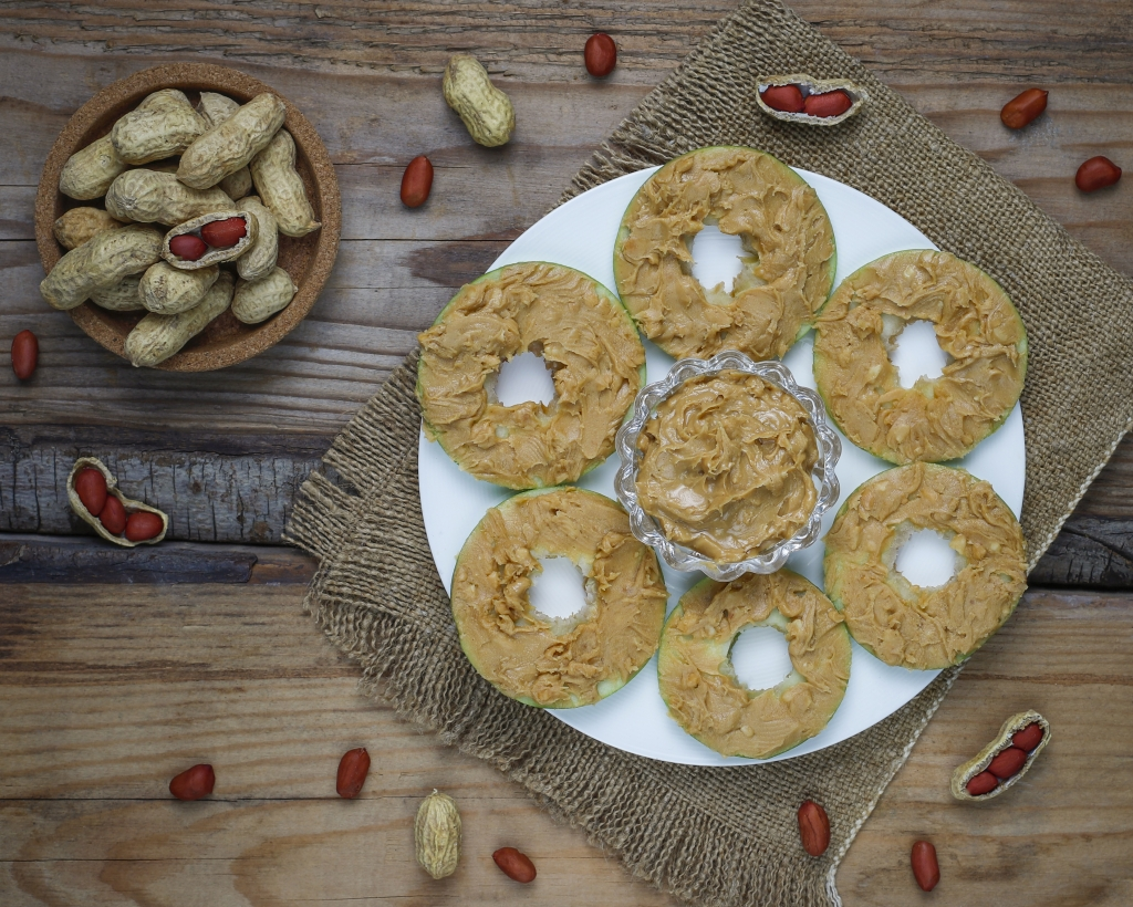 Healthy sandwich. Green apple rounds with peanut butter and red